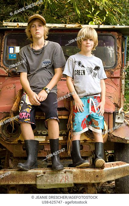 In the rain forest Two young boys ages 12 and 6 standing on an old truck wearing work boots. Osa Peninsula, Costa Rica