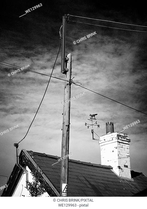 Overhead power supply to countryside cottage with weather vane on chimney in Cheshire, England, UK, Europe