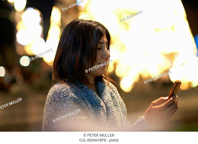 Woman using smartphone, decorative lights in background