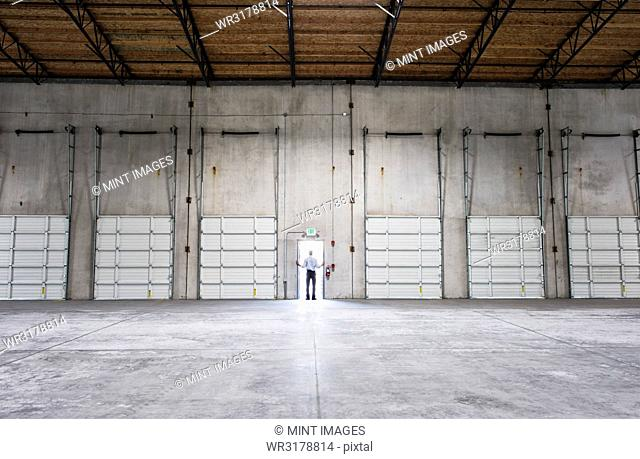 Man standing doorway of new warehouse waiting for the arrival of the fist truck with new business