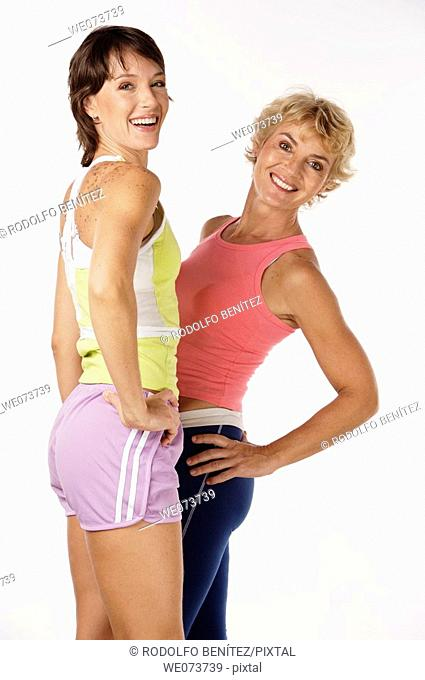 Fit mother and daughter pose in a studio setting