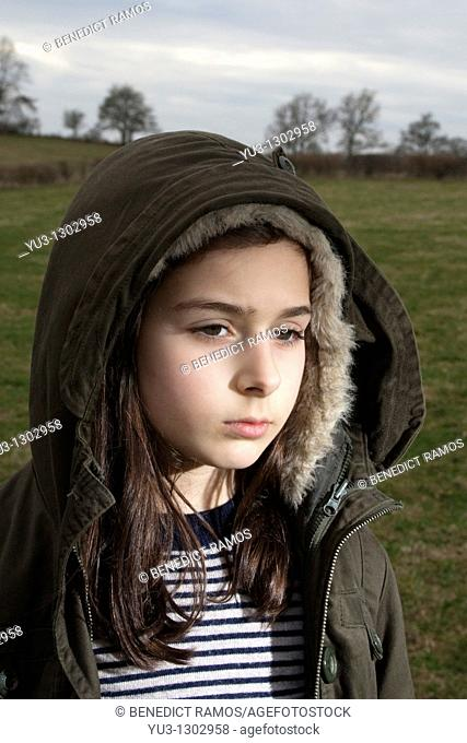 Young girl with hooded jacket standing in field