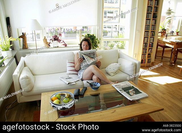 Woman reading Dagens Nyheter in the nightgown in the morning on the living room sofa