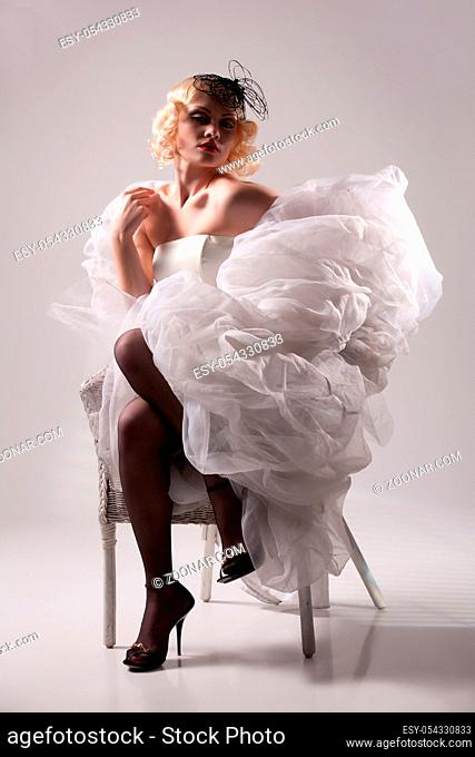 Young blonde woman in fashionable clothing in retro style on isolated background