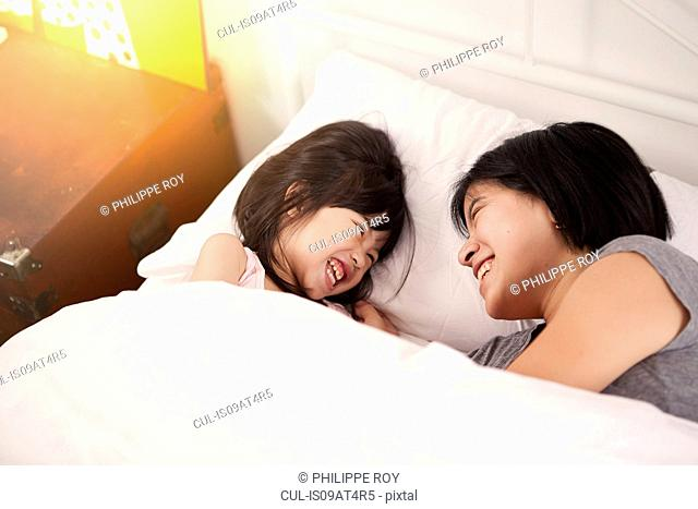 Young Chinese mother and daughter laying in bed together at home