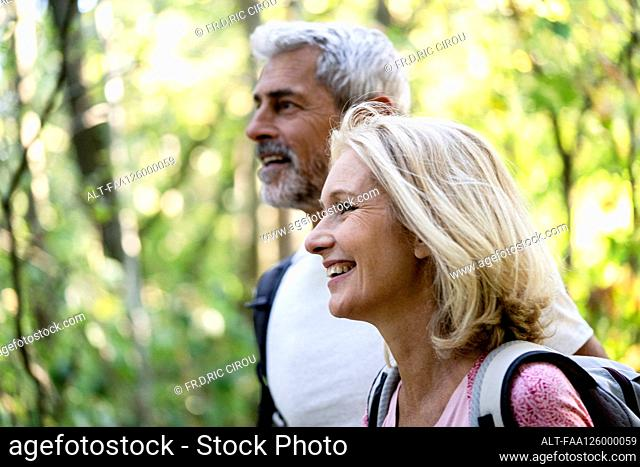 Smiling mature couple looking away in forest