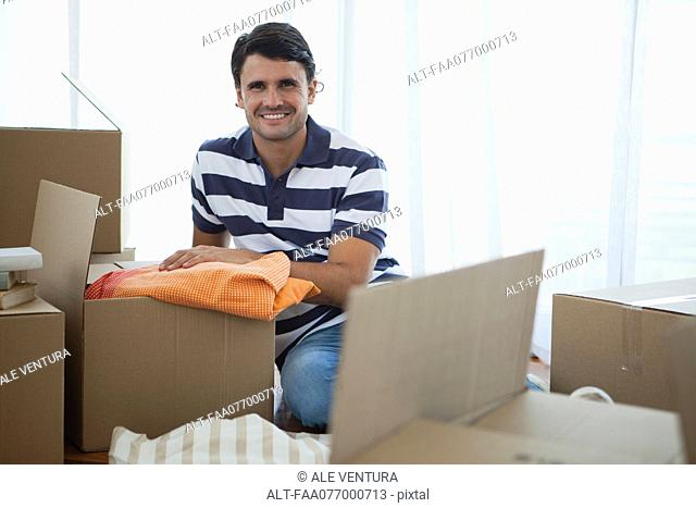 Mid-adult man unpacking in new house