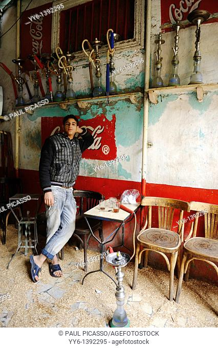 young egyptian boy standing by shisha pipes , multi coloured shisha coffee bar in islamic cairo , cairo , Egypt