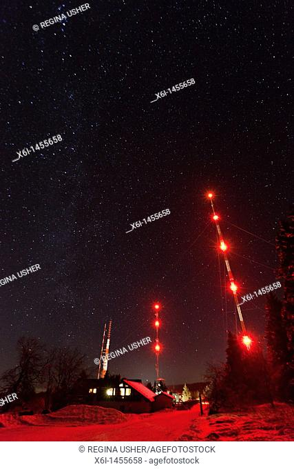 Star covered winter sky and illuminated radio masts, Hohen Meissner National Park, North Hessen, Germany