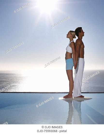 A man and woman back to back by tranquil waters