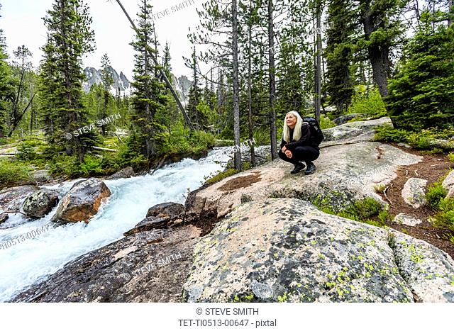 Mature woman crouching on rocks by river in Stanley, Idaho, USA