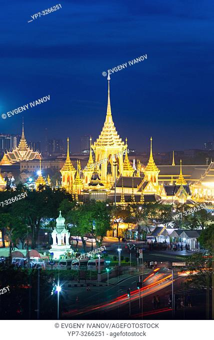 Bangkok night view from above with golden buddist temples, chedis and night traffic