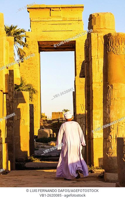 Guard in Jellabiya walking at sunset towards a monumental gate in Karkak temple, Luxor, Egypt