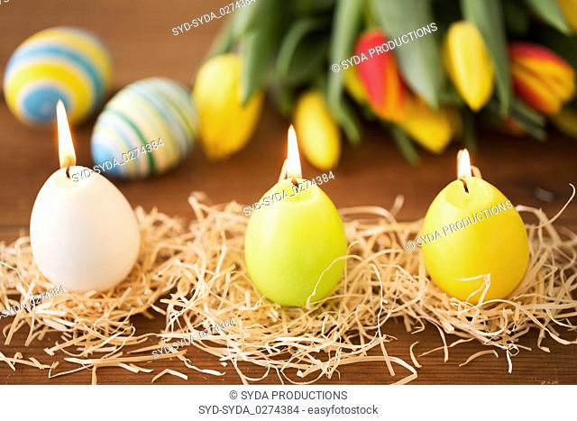 candles in shape of easter eggs and tulip flowers