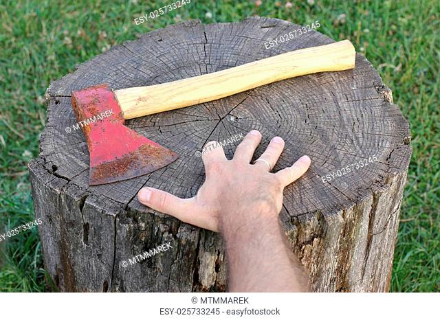 rusty axe and hand without finger lying on the stump