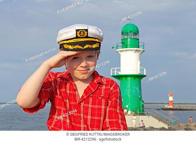 Young boy with a captain's hat, sitting in front of Lighthouse, Warnemunde, Rostock, Mecklenburg-Western Pomerania, Germany