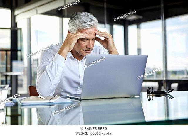 Stressed businessman sitting at desk with laptop, holding his head