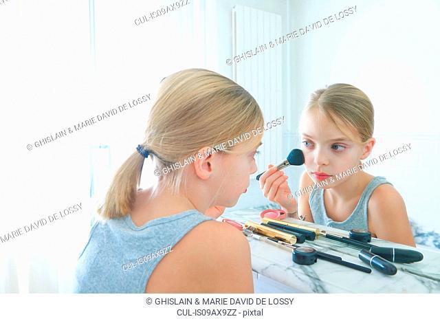 Bedroom mirror image of girl applying blusher