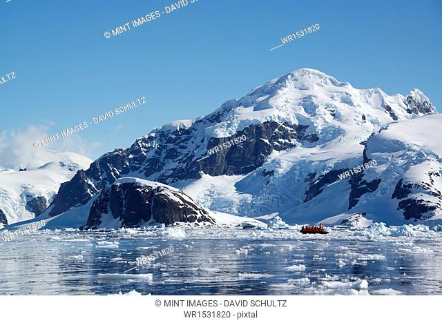 A small boat floating on the ocean among ice floes, off the shore of an island in Antarctica