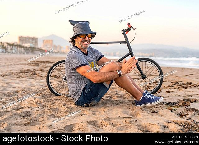 Mature man with bicycle, sitting on the beach, smiling