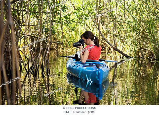Hispanic woman in kayak photographing everglades