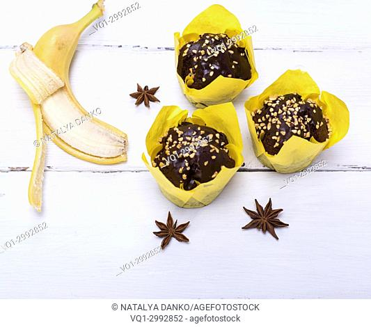 banana muffins and fresh banana on a white wooden background, top view