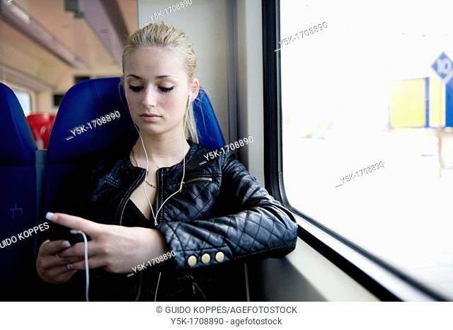 Rotterdam, Netherlands. Young, blonde woman, traveling by train from Rotterdam to Nieuwerkerk
