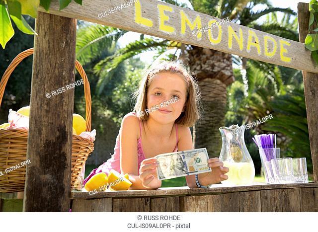 Portrait of girl on lemonade stand holding up one hundred dollar bill