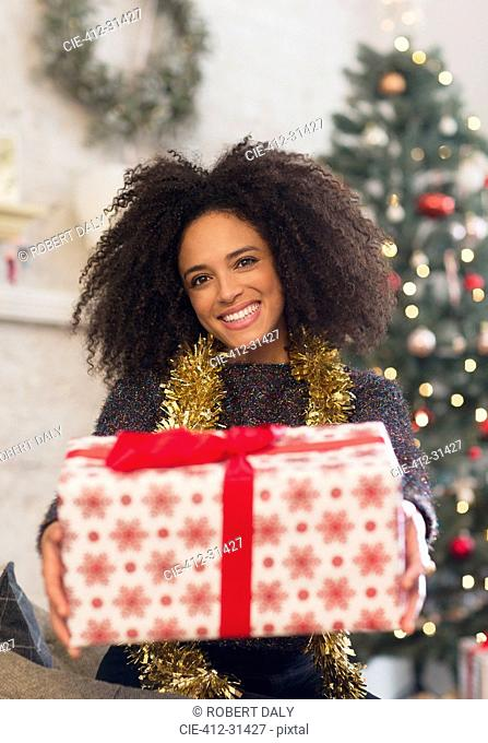 Portrait smiling woman giving Christmas gift