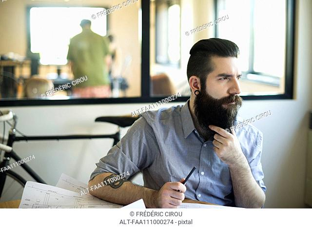 Man sitting in office, looking away in thought
