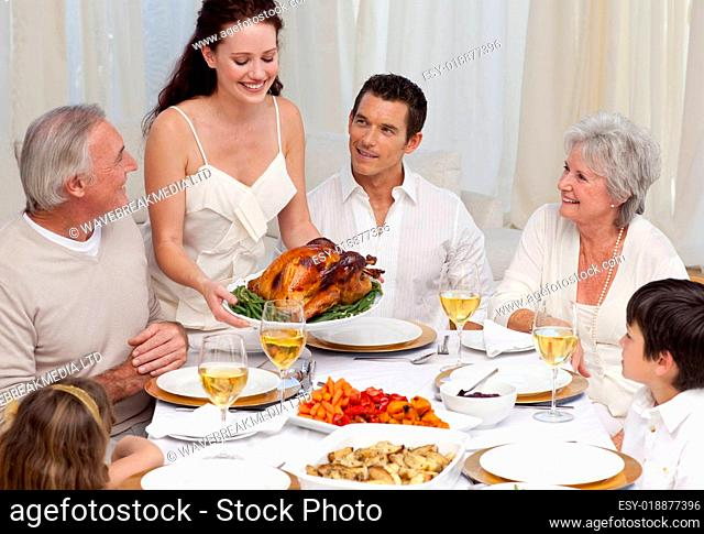 Woman showing turkey to her family for Christmas dinner