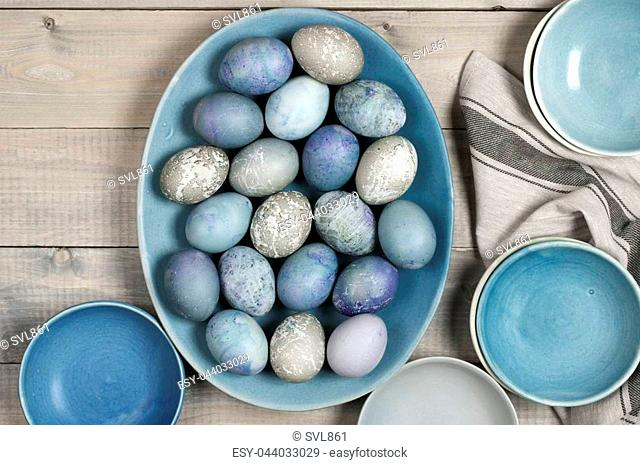 Pastel colored blue and grey Easter eggs in handmade ceramic dish, bowls and kitchen towel on rustic grey wooden background. Top view point