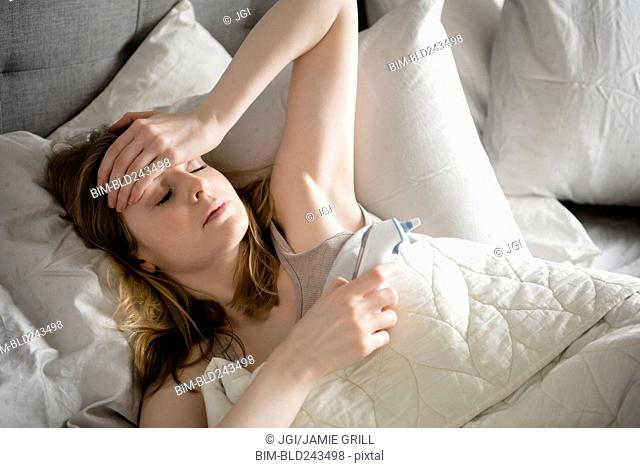 Woman laying in bed with headache