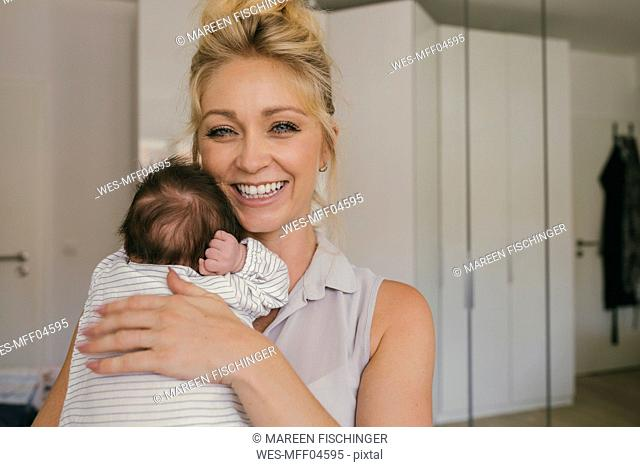 Portrait of happy mother holding her baby close to her shoulder
