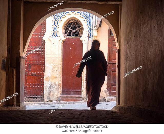Woman walking down the street in the Medina in Fez, Morrocco