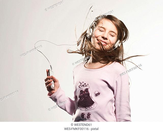 Girl 10-11 listening music, smiling