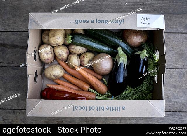 High angle close up of an organic vegetable box with a selection of fresh produce