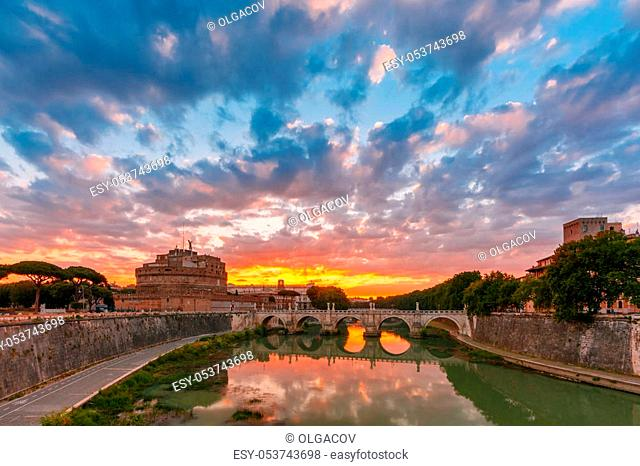 Saint Angel castle and bridge with mirror reflection in Tiber River during gorgeous dawn in Rome, Italy