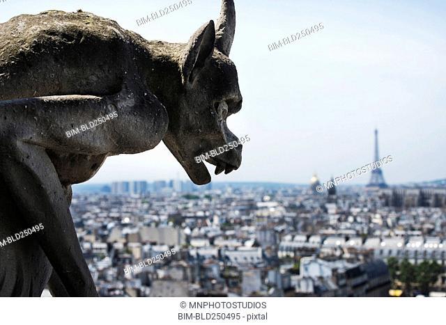Gargoyle statue overlooking cityscape