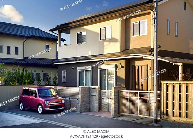 Modern Japanese private residential house exterior with a small car Suzuki Lapin parked on the driveway. Uji, Kyoto prefecture, Japan 2017