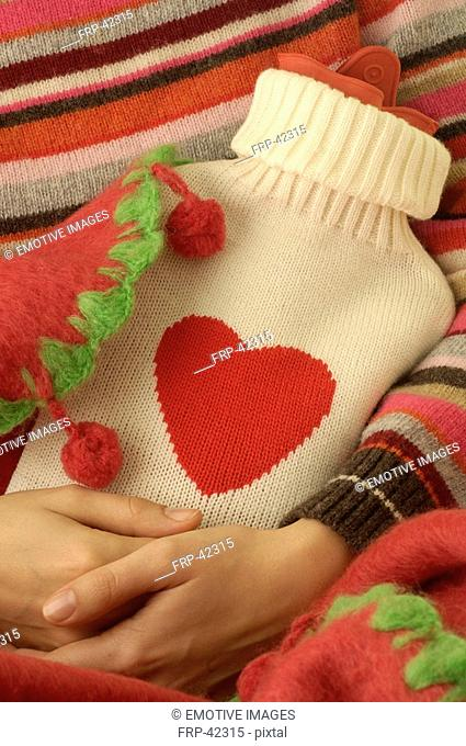 Hot water bottle in a beige overcoat with red heart