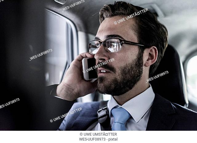 Businessman on cell phone in a car