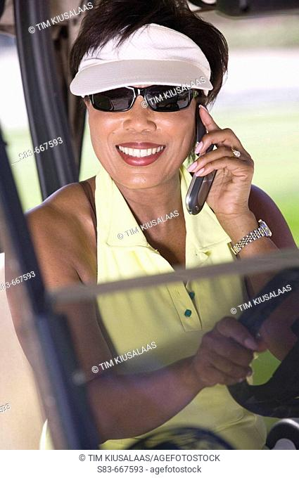 Senior woman talking on cellphone while driving golf cart