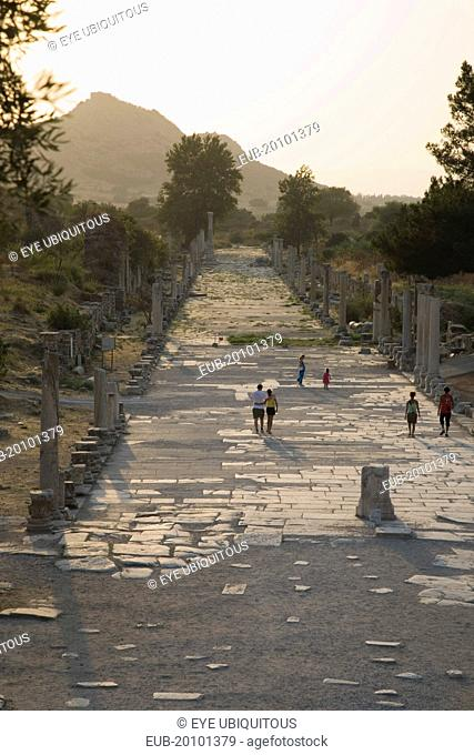 Ephesus. Tourists on paved road lined by broken columns in late afternoon sun in antique city of Ephesus on the Aegean sea coast