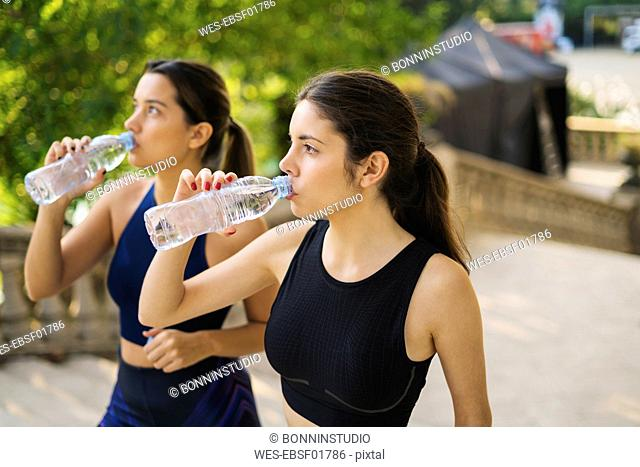 Two sportive young women drinking from bottles