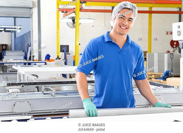 Portrait of technician worker smiling at camera on production line of solar panel factory