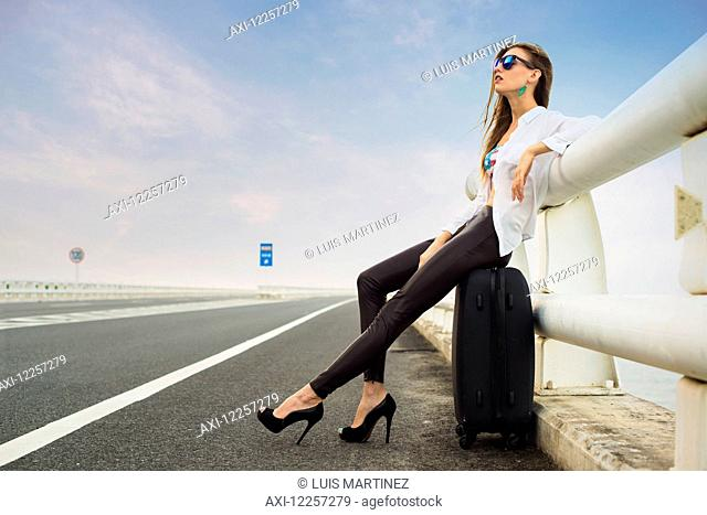 Woman hitchhiking on a highway, tired she sits in her luggage; Xiamen, Fujian, China
