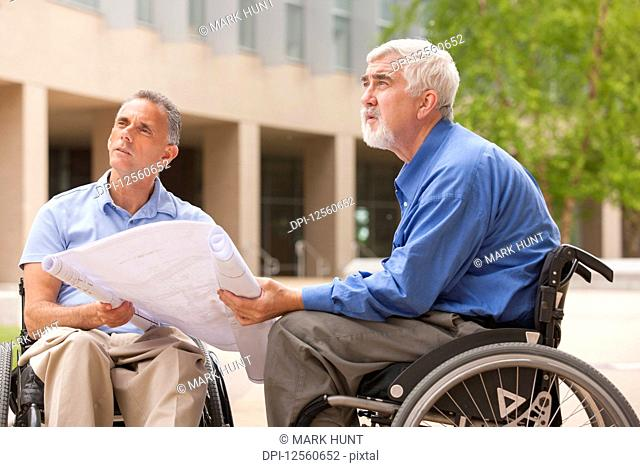 Design engineers reading Plans, one with muscular dystrophy and one with a spinal cord injury