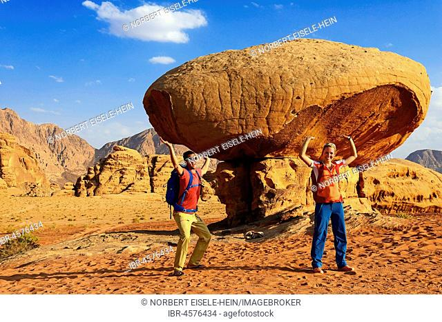 Tourists pose at Mushroom-Rock, Al Fetra, Wadi Rum, Jordan