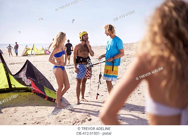 Friends learning to kiteboard on sunny beach